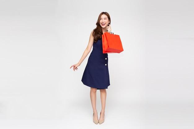 Mulher asiática segurando sacolas de compras de corpo inteiro, isolado no fundo branco