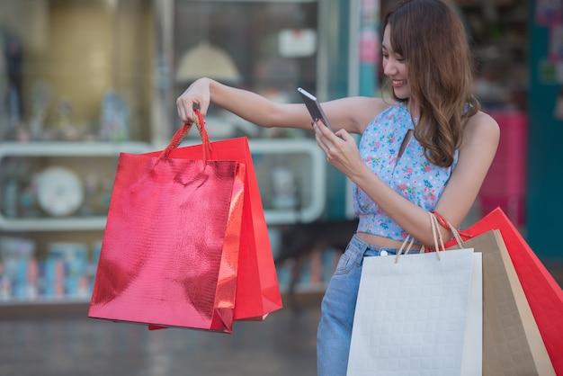 Mulher asiática segurando sacolas de compras e tirar uma foto