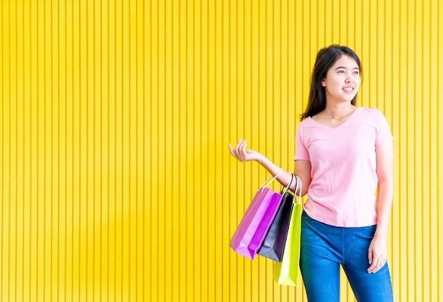 Mulher asiática segurando sacolas de compras