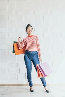 Mulher asiática, segurando sacolas de compras
