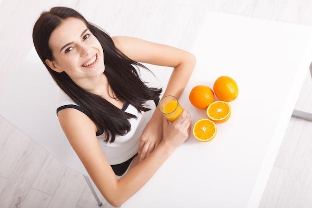 Mulher asiática segurando suco de laranja.