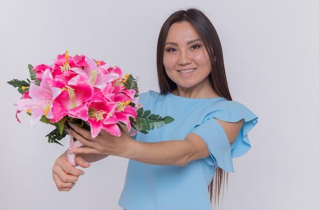 Mulher asiática segurando um buquê de flores, parecendo feliz e alegre, comemorando o dia internacional da mulher em pé sobre uma parede branca