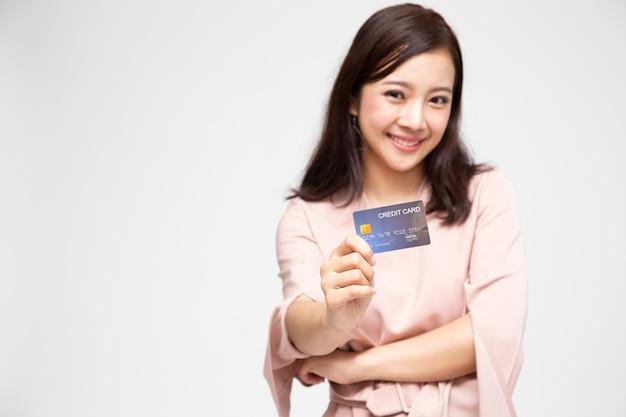 Mulher asiática segurando um cartão de crédito