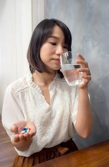 Mulher asiática segurando um copo de água e comprimidos