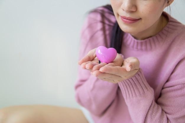 Mulher asiática segurando um coração rosa nas mãos dela.