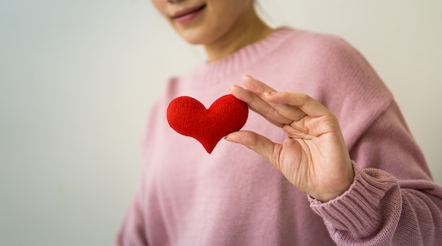 Mulher asiática segurando um coração vermelho nas mãos dela.