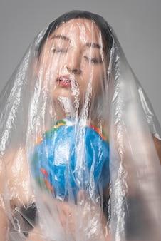 Mulher asiática segurando um globo terrestre enquanto é coberta de plástico