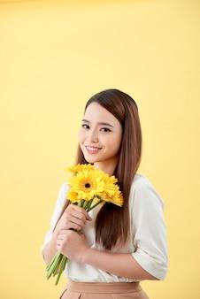 Mulher asiática segurando um ramo de flores encostada na parede