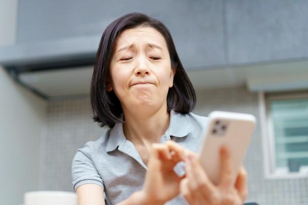 Mulher asiática segurando um smartphone com um olhar cansado na sala