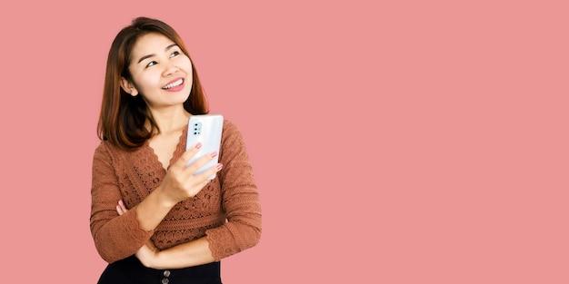Mulher asiática segurando um telefone inteligente sobre um fundo de banner rosa