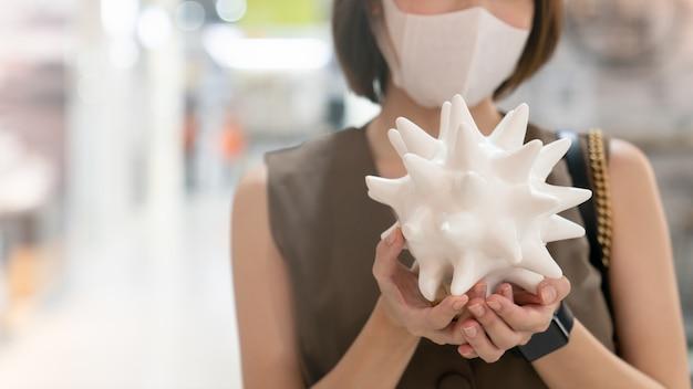 Mulher asiática segurando uma decoração de cerâmica parece coronavírus e usando máscara em uma loja de departamentos, durante uma crise de coronavírus ou surto de covid19.
