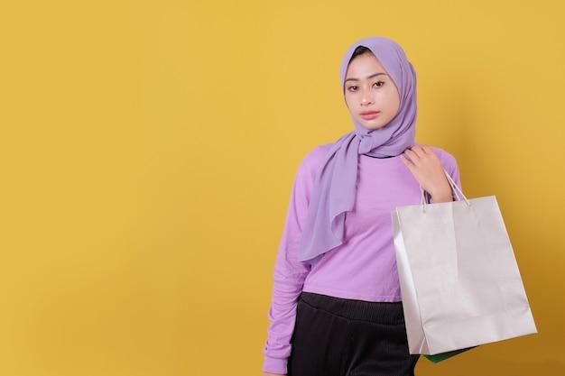 Mulher asiática segurando uma sacola de compras, vestindo uma camiseta roxa
