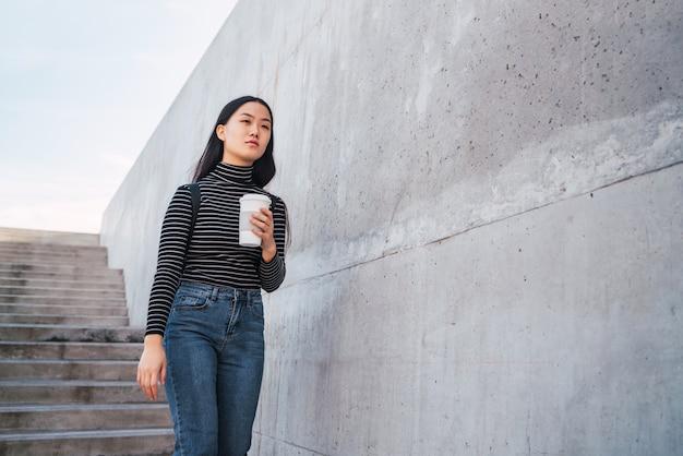 Mulher asiática, segurando uma xícara de café.