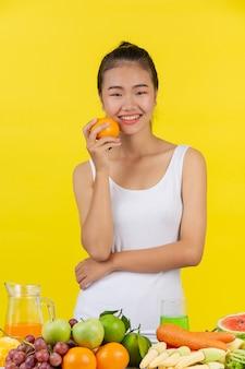 Mulher asiática segure laranjas com a mão direita, e em cima da mesa há muitas frutas.
