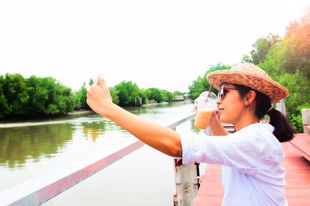 Mulher asiática selfie com copo de café gelado, viagens e estilo de vida
