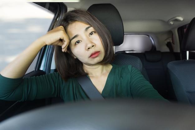 Mulher asiática sem dormir, cansada e com sono durante a condução de carro
