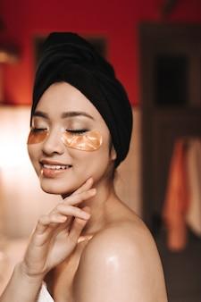 Mulher asiática sem maquiagem posando em uma toalha e com manchas douradas no lugar dos olhos