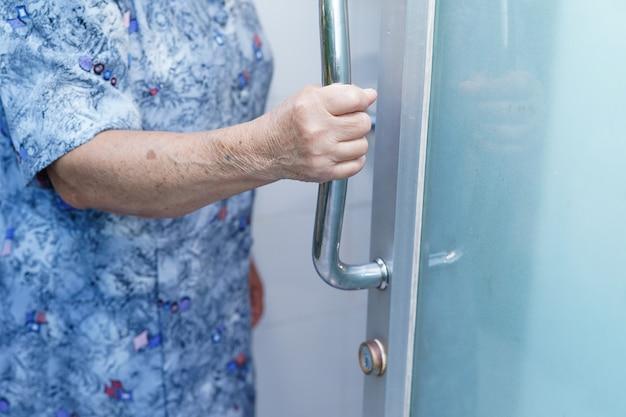 Mulher asiática sênior abre a porta do banheiro com a mão no hospital