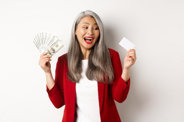 Mulher asiática sênior alegre ganha dinheiro, mostrando dólares em dinheiro e olhando para um cartão de crédito de plástico, sorrindo animada, em pé sobre um fundo branco