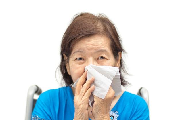 Mulher asiática sênior assoando o nariz com um lenço