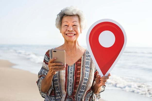 Mulher asiática sênior, check-in na praia