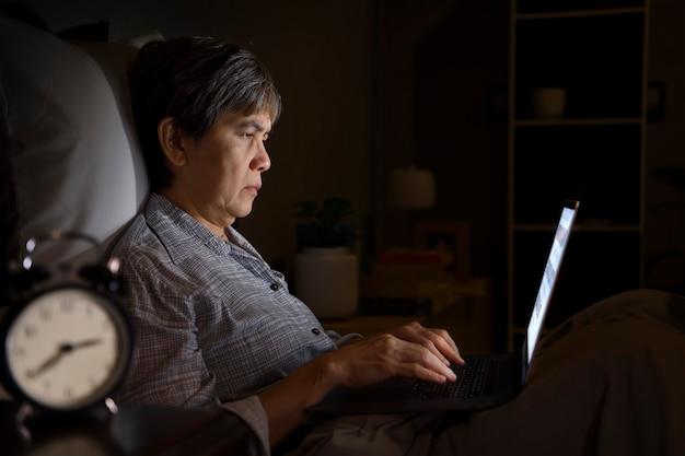 Mulher asiática sênior com olhos doloridos e cansados ao usar um laptop na cama à noite