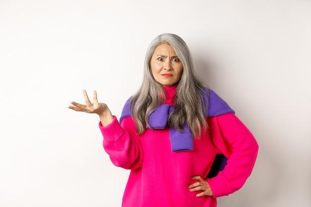 Mulher asiática sênior com raiva e confusa espalhou a mão para o lado e olhando para a câmera intrigada, em pé no suéter rosa contra um fundo branco.