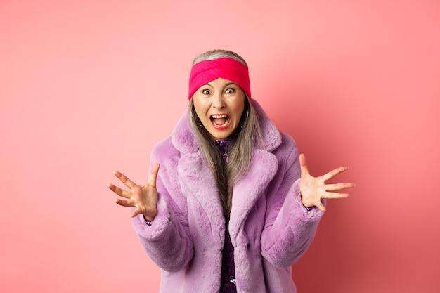 Mulher asiática sênior com raiva em um elegante casaco de pele falsa roxo, apertando as mãos e gritando para a câmera indignada, gritando com você, em pé sobre um fundo rosa.