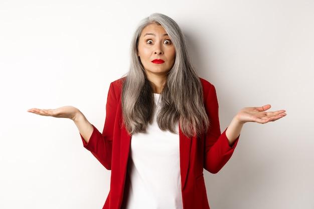 Mulher asiática sênior confusa encolhendo os ombros, espalhando as mãos para os lados e olhando questionada para a câmera, não sei de nada, em pé sobre um fundo branco