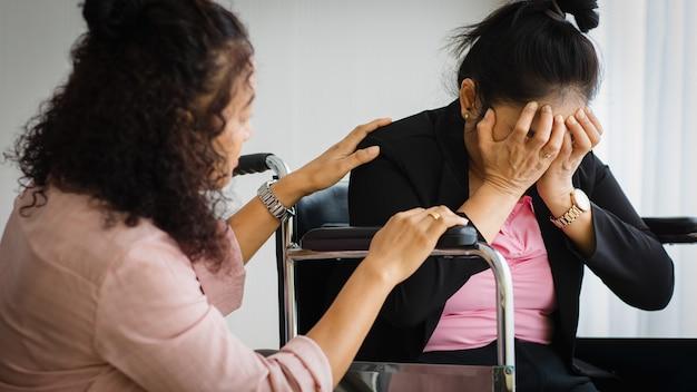 Mulher asiática sênior de meia-idade cuidar e apoiar mulheres com dores de cabeça com ataques de derrame em cadeira de rodas. conceito de problema de cérebro e cabeça.