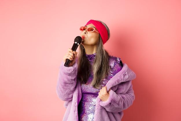 Mulher asiática sênior elegante cantando música, executando karaokê com microfone, em pé com roupa de festa e casaco de pele falsa contra fundo rosa.