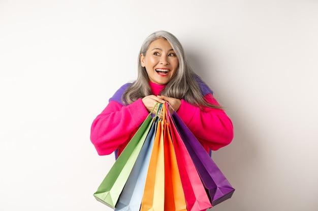Mulher asiática sênior elegante em compras, abraçando sacolas de compras e sorrindo alegre, comprando com descontos, em pé sobre um fundo branco