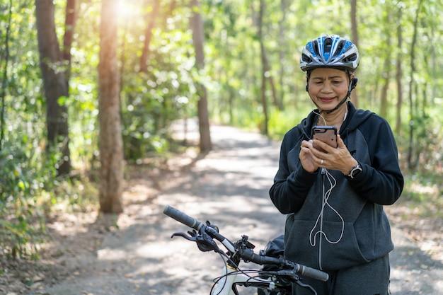 Mulher asiática sênior em bicicleta no parque