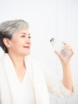 Mulher asiática sênior fazendo uma pausa durante o exercício em casa. atlética mulher madura segurando a garrafa de água.