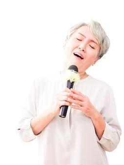 Mulher asiática sênior feliz cantando com microfone em fundo branco.