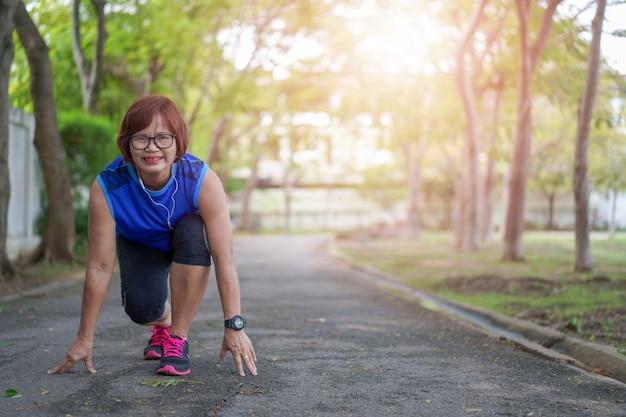 Mulher asiática sênior feliz pronto para começar a correr correndo no parque