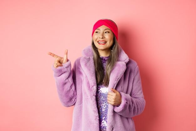 Mulher asiática sênior feliz sorrindo, apontando o dedo para a esquerda e parecendo satisfeita, verificando a promoção especial, fundo rosa.