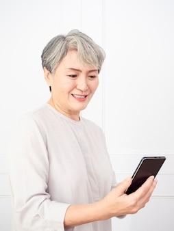 Mulher asiática sênior madura feliz segurando o smartphone usando aplicativos online móveis.