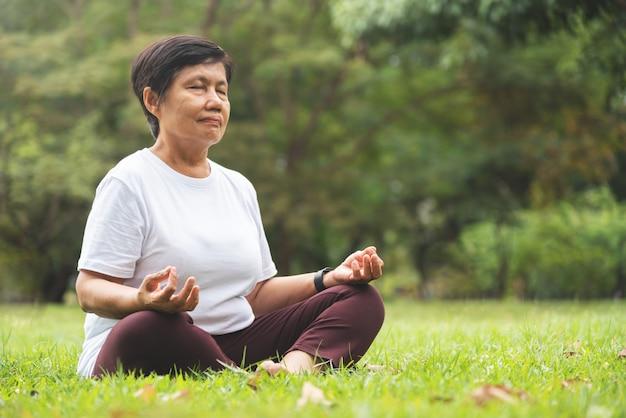 Mulher asiática sênior na camisa branca praticando ioga no parque.