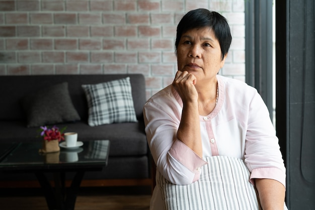 Mulher asiática sênior pensando e olhando de soslaio, pensando e imaginando