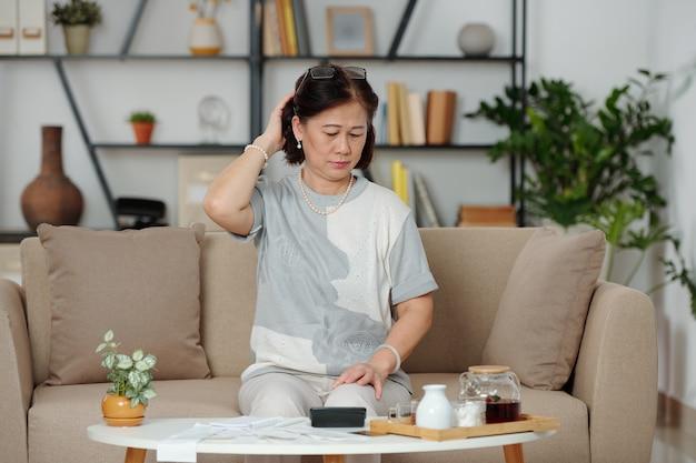 Mulher asiática sênior pensativa e confusa olhando para muitas contas na mesa de centro à sua frente