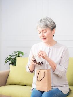 Mulher asiática sênior recebendo um colar de pérolas de presente.