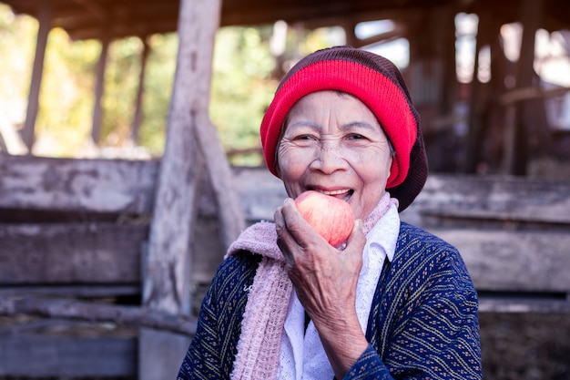 Mulher asiática sênior, segurando e comendo maçã com um grande sorriso