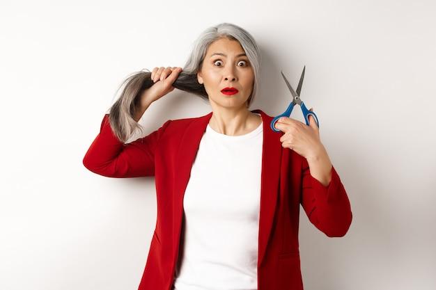 Mulher asiática sênior segurando uma tesoura e parecendo nervosa com a câmera, pensando em cortar o cabelo, mudar o penteado, em pé sobre um fundo branco