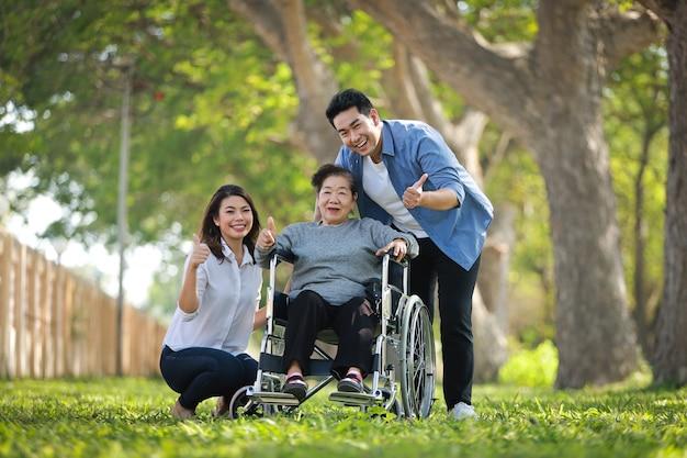 Mulher asiática sênior, sentado na cadeira de rodas com a família feliz sorriso cara no parque verde