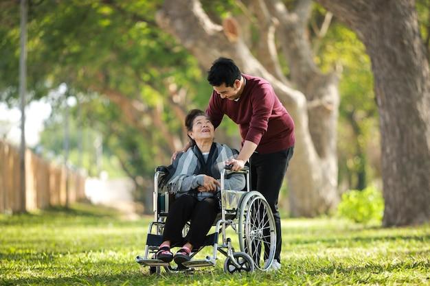 Mulher asiática sênior, sentado na cadeira de rodas com o rosto de sorriso feliz do filho no parque verde