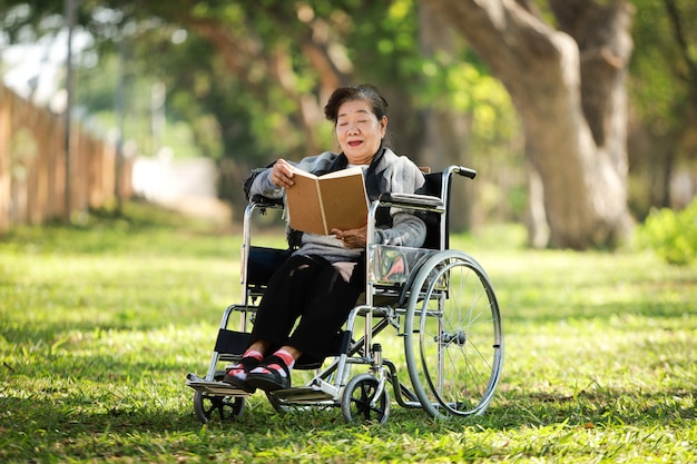 Mulher asiática sênior, sentado na cadeira de rodas, lendo o livro no parque