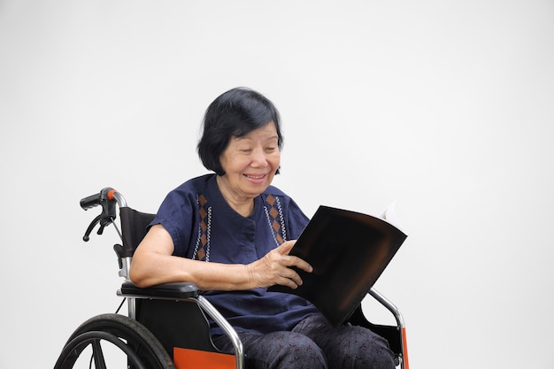 Mulher asiática sênior sorrindo enquanto lê uma revista em branco