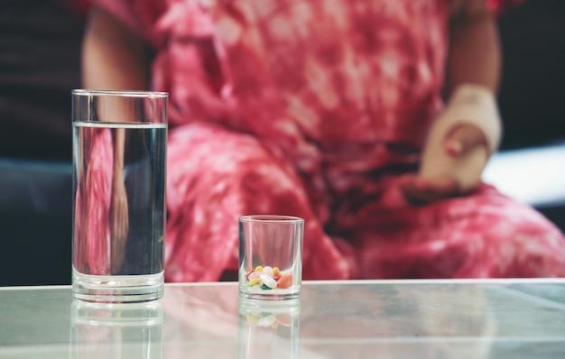 Mulher asiática sênior tomar remédio de pílula por lado