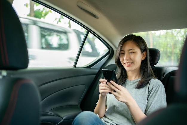 Mulher asiática sentada em um carro fica maravilhada depois de ver uma mensagem em seu celular